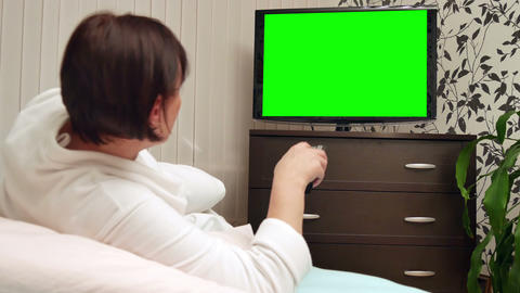 Woman watches green screened TV. Dolly shot Footage