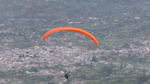 solo paraglide flying against populated area in Andes Footage
