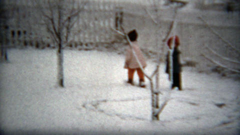 1960: Kids leaving fresh tracks in winter snow in white fenced backyard Footage