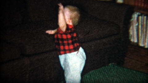 1960: Young baby boy first steps cruising along a couch while waving and laughin Footage