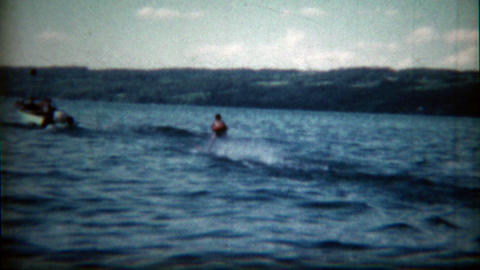 1960: Child helped up by mom to waterski for the first time Footage