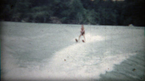 1960: Boy waterskis behind boat showing off his latest tricks Footage