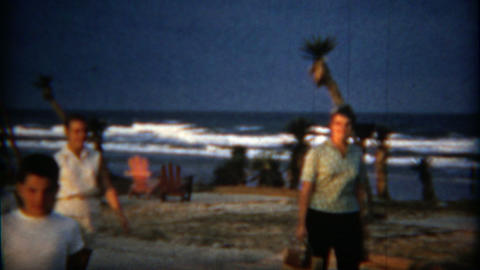 1960: Family running on beach to campsite screen tent car trailer setup Footage