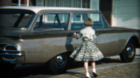 1961: Girl dressed in polka dot skirt showcasing new family station wagon Ford c Footage