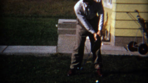 1957: Man practicing ugly golf swing in suburban backyard Footage