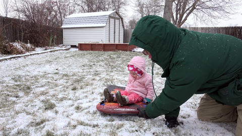 Baby girl in pink riding snow sled closeup pulled in backyard winter storm Footage