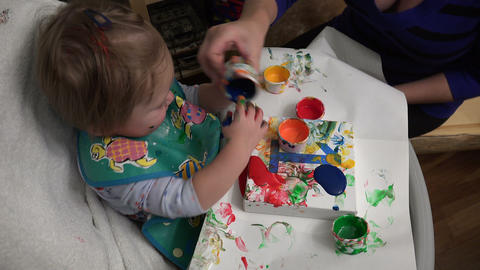 Baby dumping paint everywhere attempting to finger paint for 1st birthday Footage