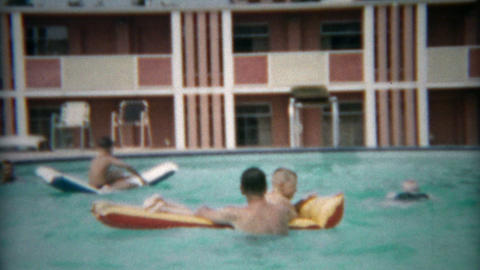 1955: Dad playing with kids in hotel pool with inflatable raft Footage