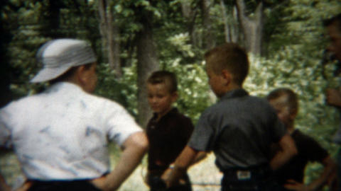 1955: Boys tending campfire during the warm summer day in the park Footage