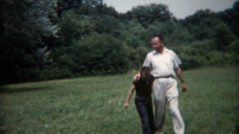 1955: Father and son practicing for a 3 legged race at the summer camp Footage