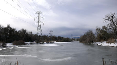 Timelapse drone buzzing around winter frozen pond cloudy industrial electric pow Footage
