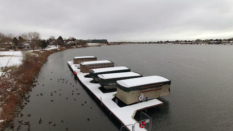 Aerial drone fly over lake snow covered boating dock covers secured for the wint Footage