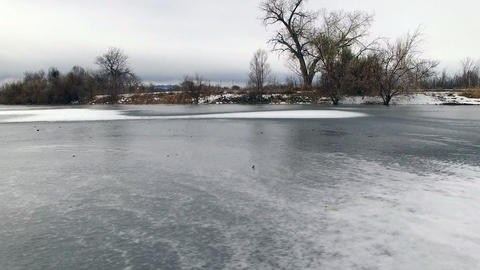 Aerial drone sideways movement across ice covered water pond cloudy gray sky Footage