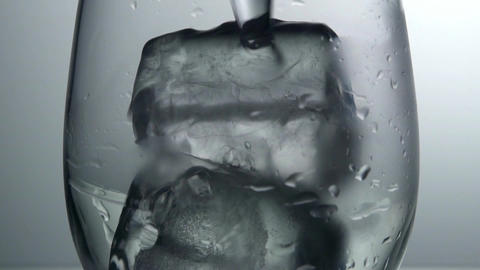 Close up of water into glass with ice cubes, slow motion Footage