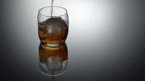 ouring whiskey into glass with ice cubes, slow motion Footage