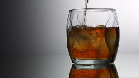 Pouring whiskey into glass with ice cubes, slow motion Footage