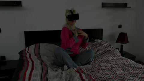 Pretty young woman playing game using virtual glasses in bedroom Footage
