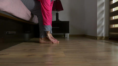 Feet of a woman getting out of bed in the morning touching the floor and getting Footage