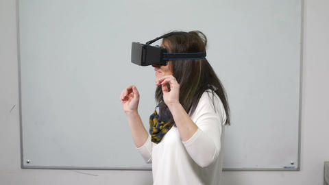 Female playing a video game with VR 3d special equipment headset during test Live Action