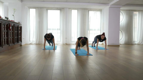 Teacher and two learners doing yoga sequence together during class Footage