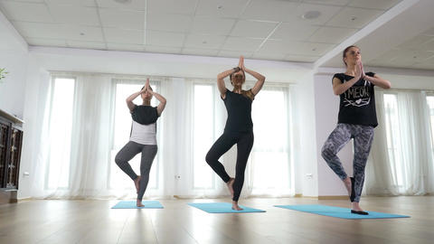 Girls practising balance in tree pose during yoga class at the gym Footage