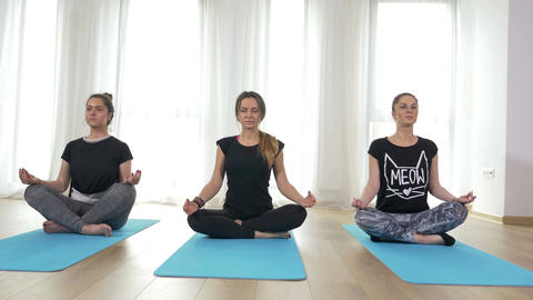 Three beautiful young women standing in lotus position on the mat at the gym Footage