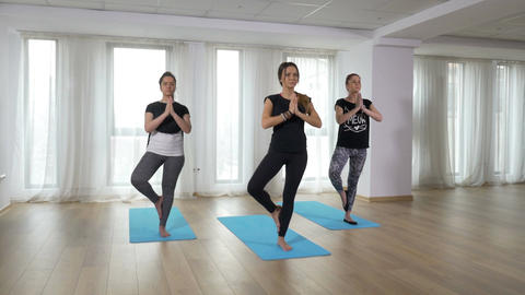 Young women practicing vrikshasana at the gym Footage