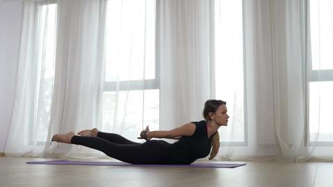 Young blonde adult woman doing bow pose during yoga workout Footage