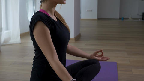 Woman sitting in meditation lotus pose in a yoga gym Footage