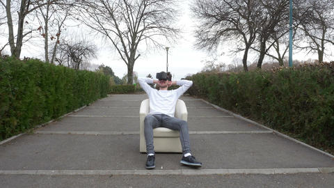 Student sitting relaxed in an armchair in a park wearing virtual reality glasses Footage