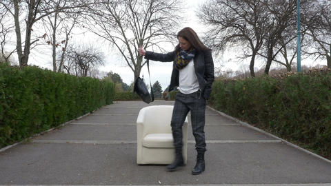 Woman walking into the park finds an armchair on an alley and rests in it Footage