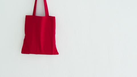 Handbag hanging on white wall Live Action