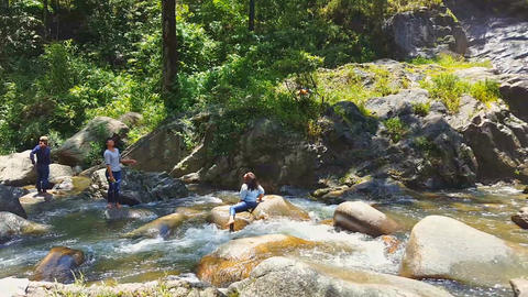 Asian People Sit on Big Rocks in Mountain River Footage