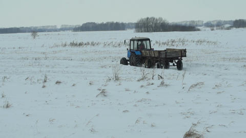 Rural scene. Tractor with trailer rides on snow field Footage