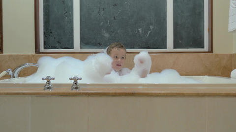 Playful child having bath with foam 画像