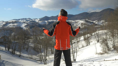 Man making arms raised victory gesture while admiring a winter landscape at the  Footage