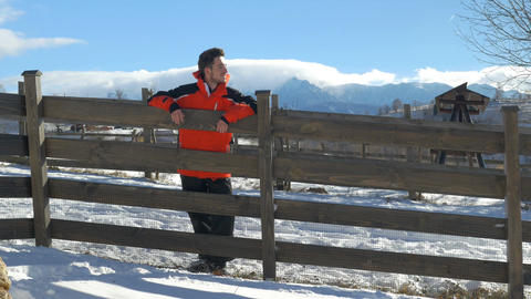 Young man smiling and leaning on a fence in a beautiful winter day at the countr Footage