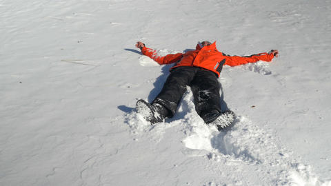 Young man throwing himself in the snow and making snow angels Footage