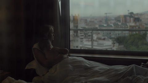 Mom and son looking at evening city lying in bed Footage