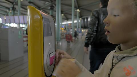 Child using ticket scanning machine Acción en vivo