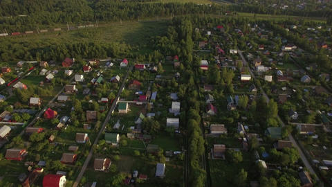 Flying over village houses and moving cargo train Footage