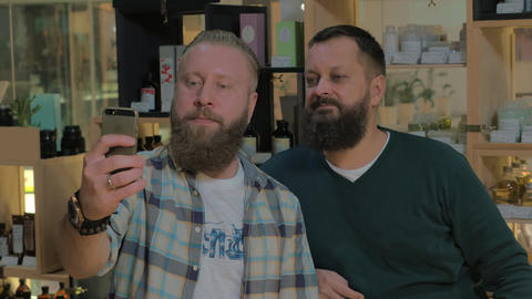 Two bearded men taking mobile selfie indoor Live Action