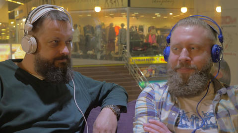 Two bearded men listening to music in headphones Footage