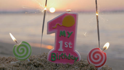Baby girl first birthday candle on the beach Footage
