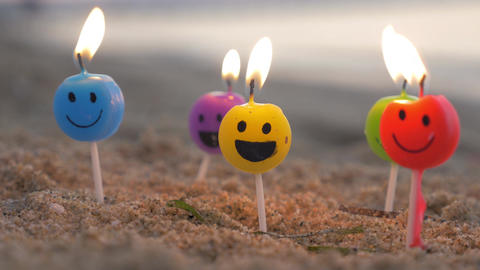 Burning smiley candles on the beach Footage