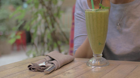 Drinking mint smoothie in cafe Footage