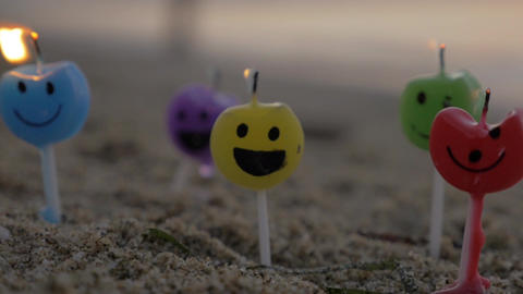 Colorful smiley candles on the beach Image