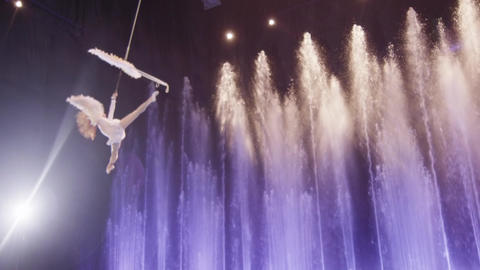 Aerial performer making acrobatic act against colorful fountains, acrobatics, Footage