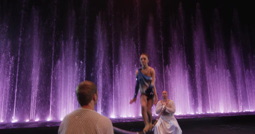 Group of acrobats making act with pole against colorful fountains, Moscow, Footage