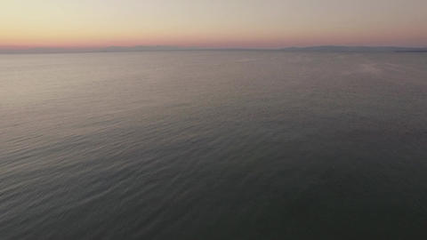 Aerial flight above the water of the sea against horizon line Live Action
